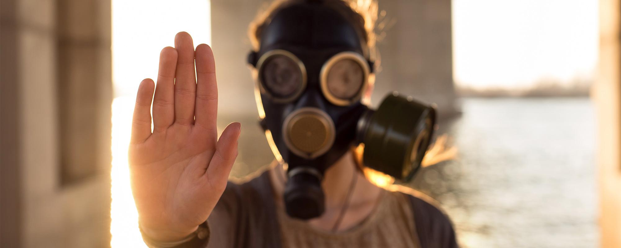 man wearing gas mask hand up
