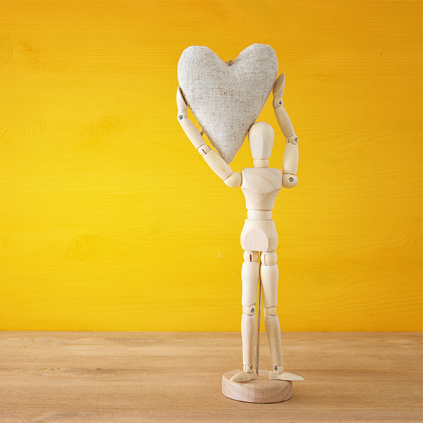 wood figure holding wood heart